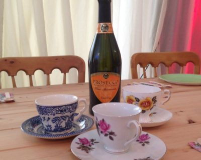 a display of a fine bottle of prosecco and some vintage teacups