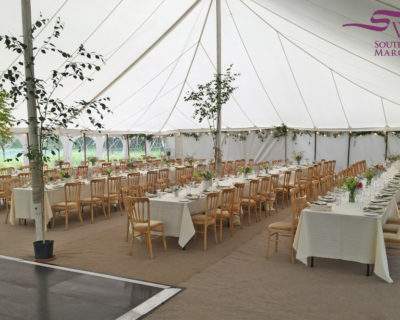 Natural wood banquet chairs in traditional marquee