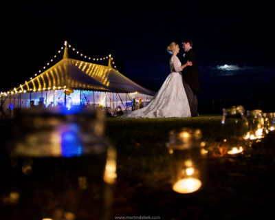 bride and groom outside marquee at night