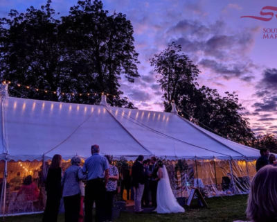 traditional marquee at night with bride and groom